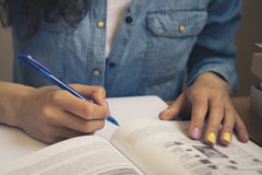 Girl in a denim shirt reading a textbook and taking notes. Girl in a denim shirt sitting at the table, reading a textbook and taking notes with a pen on a sheet Royalty Free Stock Photos
