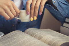 Girl in a denim shirt sits at the table and reading a book. In her hands with a bright manicure Cup of coffee. On the table an open book. Closeup. Vintage Stock Photos