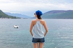 Girl in denim shorts is standing with his back against the background of the Bay Stock Images
