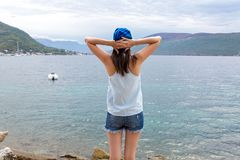 Girl in denim shorts is standing with his back against the background of the Bay Stock Photos