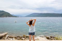 Girl in denim shorts is standing with his back against the background of the Bay Stock Photography