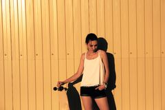 Girl in denim shorts and tank top standing with skateboard in front of yellow mwtal fence and looking down Stock Photography