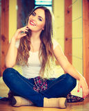 Girl in denim trousers sitting on floor Royalty Free Stock Photography