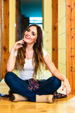 Girl in denim trousers sitting on floor Stock Images