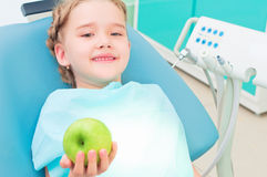 Girl in the dentist's chair shows a green apple Royalty Free Stock Photo