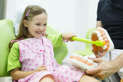 Girl in dentists chair toothbrushing a model Royalty Free Stock Photography
