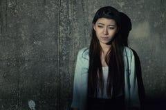 Girl in depression , grief , despair, discouragement , despair. A concrete wall background lighting was dim Stock Images