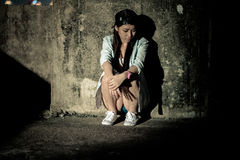 Girl in depression , grief , despair, discouragement , despair. A concrete wall background lighting was dim Royalty Free Stock Photos