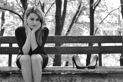 Girl in depression outdoors. Portrait of worried woman siting on bench in park. Depression after the divorce or losing someone Royalty Free Stock Image