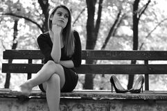 Girl in depression outdoors. Portrait of worried woman siting on bench in park. Depression after the divorce or losing someone Stock Photo