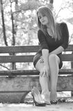 Girl in depression outdoors. Portrait of worried woman siting on bench in park. Depression after the divorce or losing someone Royalty Free Stock Photography