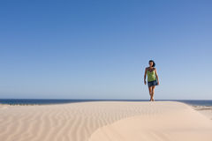 Girl in desert. Young girl is walking over the Stockton dunes in Anna Bay, NSW, Australia. The ocean is visible at the distance stock photos