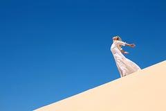 Girl in desert. Girl in white dress on dune Stock Image