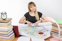 Girl design student at his desk with smile turns to roll the finished drawing project Royalty Free Stock Photos