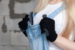 Girl designer foreman blonde in construction helmet, textile black protective gloves, denim overalls standing near gray wall Cibit. Girl designer foreman blonde royalty free stock photo