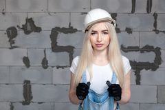 Girl designer foreman blonde in construction helmet, textile black protective gloves, denim overalls standing near gray wall Cibit. Girl designer foreman blonde royalty free stock photos