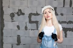 Girl designer foreman blonde in construction helmet, textile black protective gloves, denim overalls standing near gray wall Cibit. Girl designer foreman blonde stock image