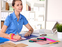 Girl Designer in an Office behind a table Royalty Free Stock Images