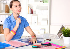 Girl Designer in an Office behind a table Royalty Free Stock Image