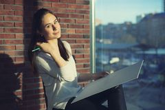 Girl designer sitting on a chair by the window and draws a sketch works as an artist stock photo