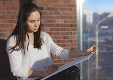 Girl designer sitting on a chair by the window and draws a sketch works as an artist stock photos