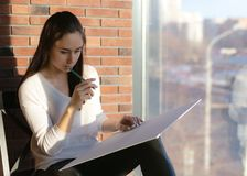 Girl designer sitting on a chair by the window and draws a sketch works as an artist royalty free stock image