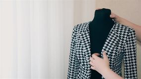 Girl designer women`s clothing on a mannequin straightens black and white jacket HD. Girl designer women`s clothing on a mannequin straightens black and white stock footage