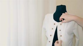 Girl designer women`s clothing put on a mannequin jacket in white. Woman designer women`s clothing trying on clothes on a mannequin stock video