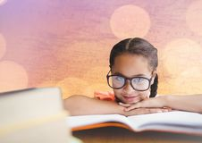 Girl at desk with books against map with bokeh Royalty Free Stock Photo