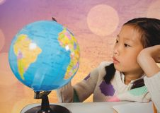 Girl at desk with globe against map with bokeh Royalty Free Stock Photo