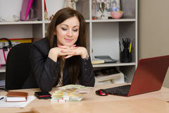 The girl at desk looking a stack of money Royalty Free Stock Photo