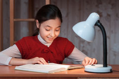 Girl at desk reading a book by light of lamp Stock Photos