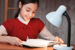Girl at desk reading a book by light of the lamp Stock Photography