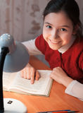 Girl at desk reading a book by light of the lamp Stock Photo
