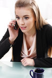 The girl at the desk talking on. The phone Royalty Free Stock Photos