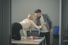 Girl on desktop seduce man in office. Girl dominating man at workplace, matriarchy. Girl on desktop seduce men in office. Girl dominating men at workplace stock photography