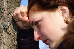 Girl in despair. Leaned against a tree, side view Royalty Free Stock Image
