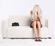 Girl in despair. Full-length portrait of depressed beautiful young blond woman sitting on couch and hiding her face in hands and hair Royalty Free Stock Photography