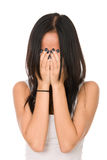 Girl in despair shuts face with hands. Isolated on white background Stock Photos