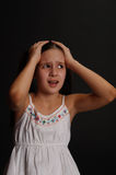 Girl in despair. Girl in a white dress on a black background in despair Royalty Free Stock Image