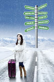 Girl with destination choices for holiday. Lovely girl in winter clothes standing on the road with destination choices for winter holiday Royalty Free Stock Image