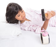 Girl Destroy Alarm Clock II. Irritated young Asian Malay girl waking up from sleep and destroying alarm clock royalty free stock image