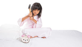 Girl Destroy Alarm Clock V. Irritated young Asian Malay girl waking up from sleep and destroying alarm clock royalty free stock images