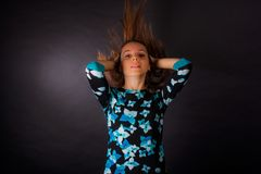 The girl with developing long hair on black background stock photo
