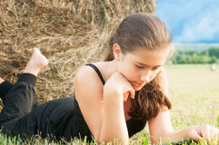 Girl with  device laying close  to haystack Royalty Free Stock Image