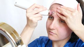 A girl with a device performs microdermabrasion of the skin of the face on a white background, sitting with a mirror