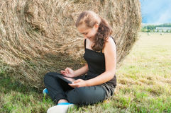 Girl with  device siting close  to haystack Stock Photography