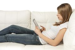 Girl with device. On white background beautiful girl with devices on the sofa Royalty Free Stock Photography