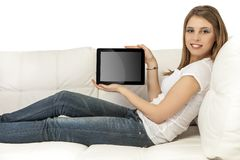 Girl with device. On white background beautiful girl with devices on the sofa Royalty Free Stock Image