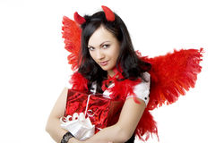 Girl in a devil costume with a gift. Picture of a girl in a devil costume with a gift royalty free stock images